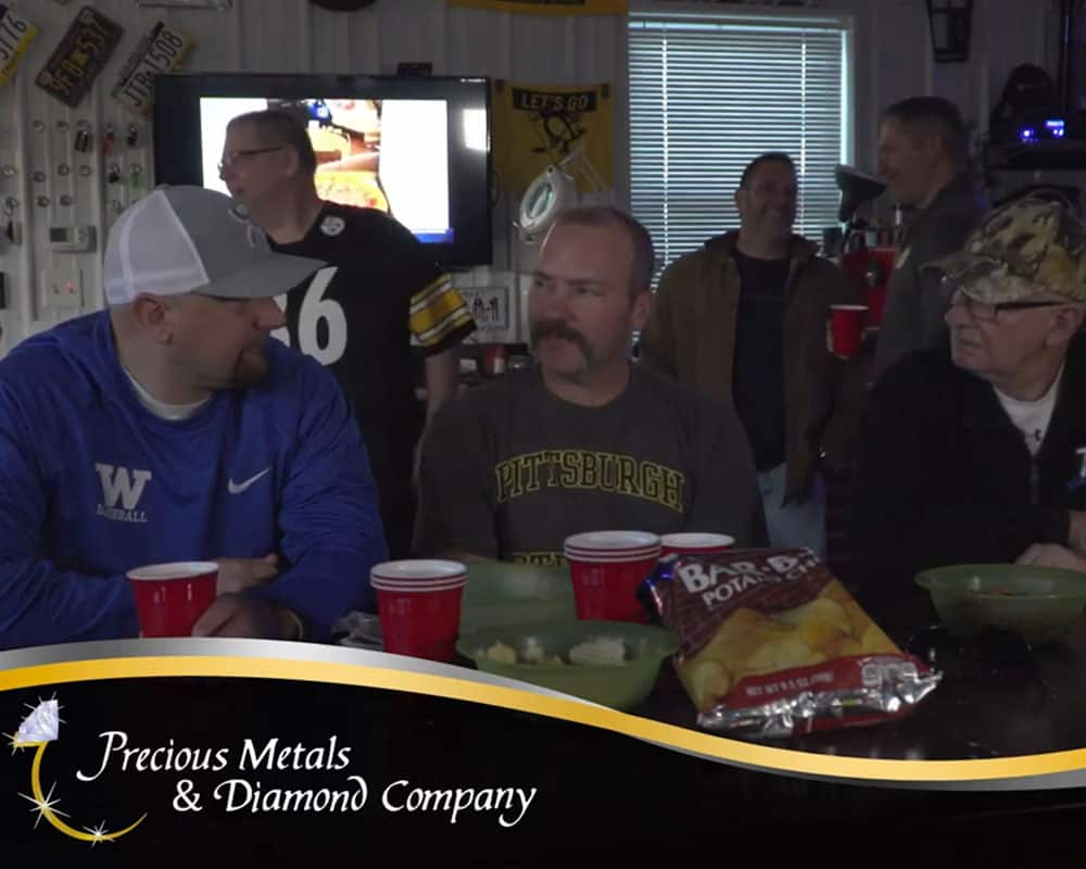 Still from Precious Metals & Diamond Company commercial, men in a garage watching football